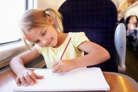 girl drawing while traveling on a train