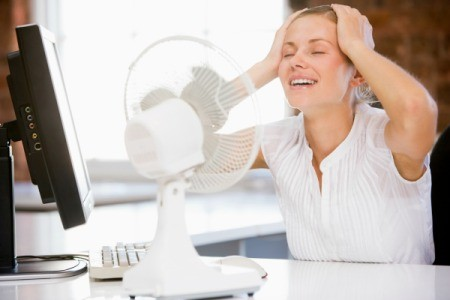 Woman Using Fan to Cool Off