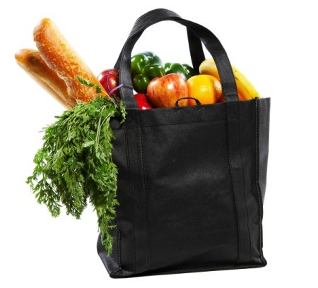 black shopping bag filled with fruit, veggies, and loaves of bread