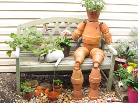 Terra cotta flowerpot man sitting on garden bench
