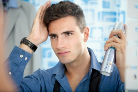 young man using hairspray in front of mirror