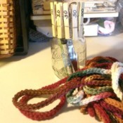 glass jar with clothes pins behind crochet chain