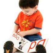 young boy looking at an alphabet book