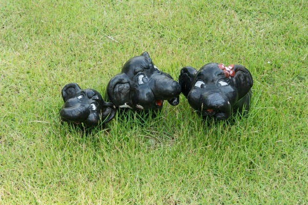 three cute black plaster elephants in the grass