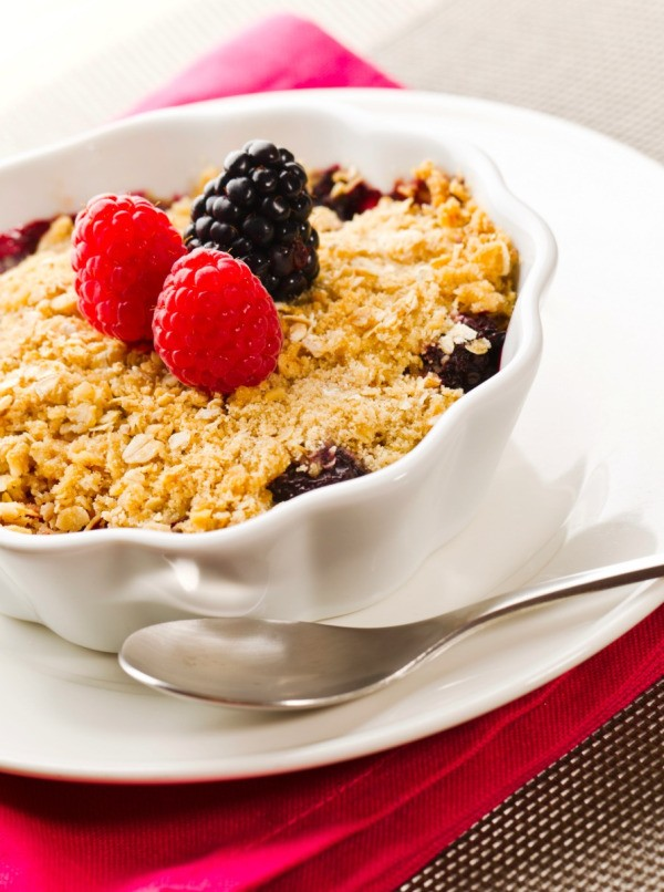 mixed berry cobbler in  white scalloped dish
