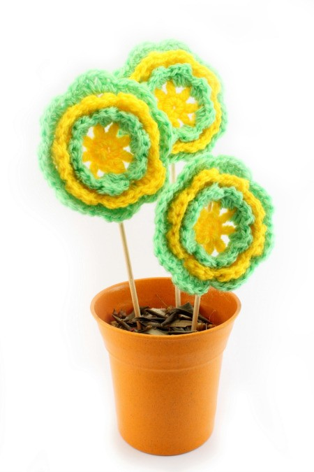 green and yellow crocheted flowers in pot