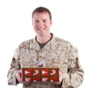 young man in camos holding a Christmas gift