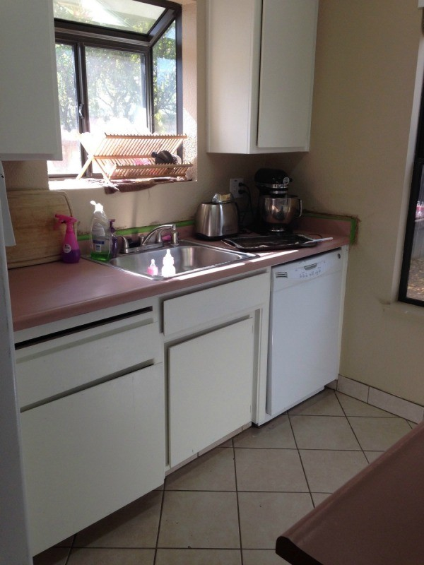 view of pink countertop and cabinets