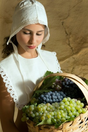 girl wearing a bonnet holding a basket of grapes