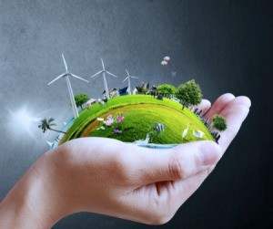Hand holding green earth with city, wind turbines, etc. against a grey background