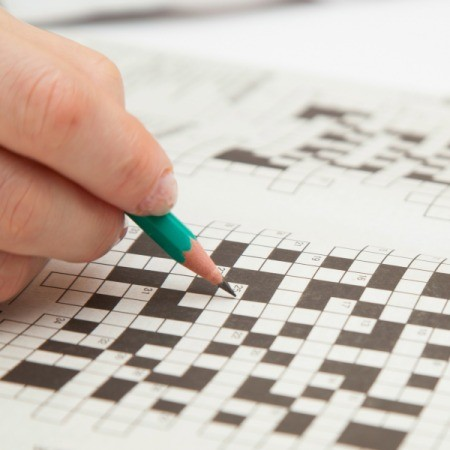 a person doing a crossword in pencil