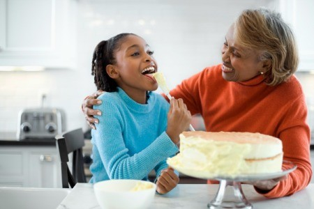 Grandmother and Granddaughter Icing a Cake