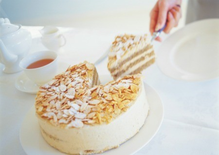 cutting a slice of almond cake