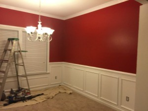 dining room with red walls and white wainscoating