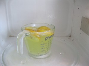 Lemon and Baking Soda for Cleaning Microwave - A measuring cup with cut up lemons, water and baking soda.