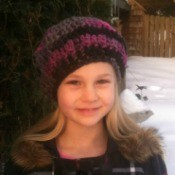 A girl wearing a crocheted beret outside in winter.