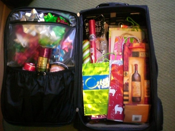 Open suitcase with gift wrap stored inside.