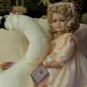 doll sitting on a swan