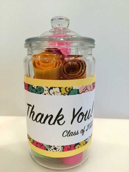 glass jar with lid containing brightly colored rolls of paper with messages for teacher