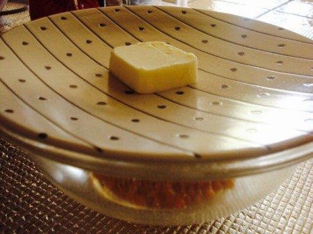 A pat of butter on a microwavable plate.