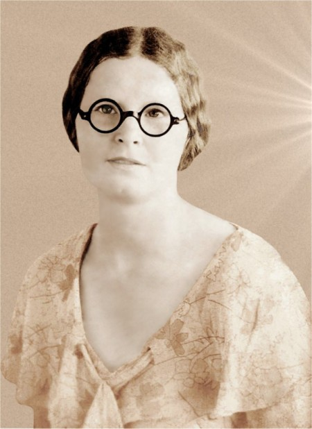 An old fashioned black and white photo of a woman in glasses.