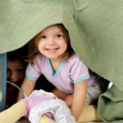 children playing in a playhouse made from a table and blanket