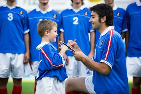 child getting soccer player's autograph