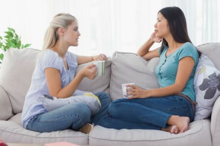 2 women talking on couch