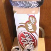 A long soda box with the flaps tied back.