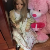 doll next to a pink stuffed bear