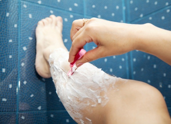 female hand shaving legs