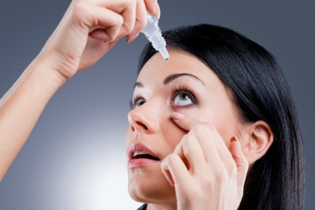 woman using eyedrops