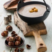 cast iron pot of soup with chestnuts scattered about
