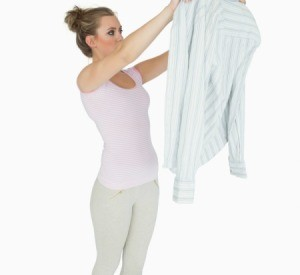 A woman inspecting a snagged shirt.