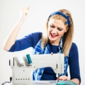 Photo of a woman with a broken sewing machine that won't go in reverse.