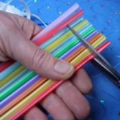Cutting straws to make small sections for the necklace.