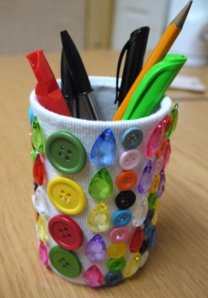 A pencil pot decorated with gems and buttons.