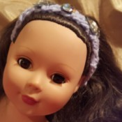closeup of doll wearing the finished headband
