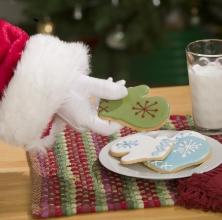 Photo of Santa picking up a cookie.