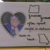 A wooden frame with a heart shaped opening, decorated with two state outlines and a quote.