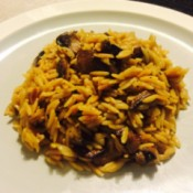 A plate of orzo risotto with mushrooms and cheese.
