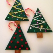 two sequin and one pom pom decorated felt Christmas tree treat holders