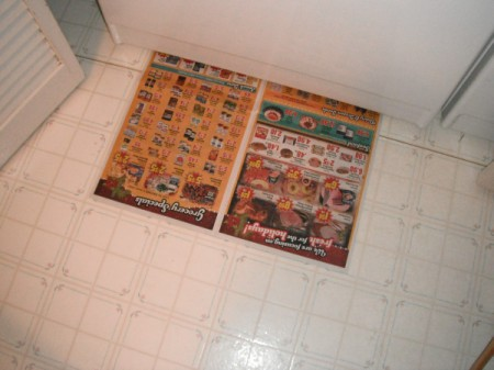 newspaper on floor in front of freezer
