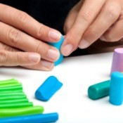 A photo of hands molding multi-colored polymer clay.