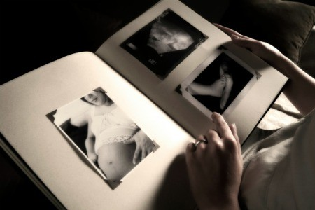 Black and white image of hands holding a book with three pictures - a pregnant mother, an ultrasound, and babu feet.