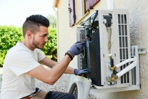 Man repairing an exterior home  air conditioning unit