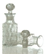Two clear cut crystal decanters on a white background.  One is upright with stopper inserted.  The other is on it's side with it's stopper laying next to it.