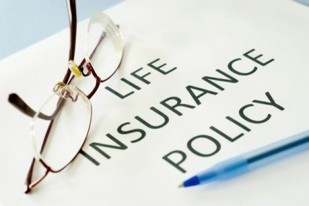 "White paper with ""LIFE INSURANCE POLICY"" in bold typeface.  A folded pair of glasses and a pen rest on the paper."