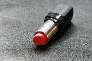 Opened tube of Red Lipstick on black leather surface