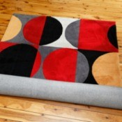 Brightly colored black, red, grey, yellow, and white area rug partially unrolled on a wood floor